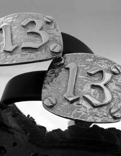 Pulsera en plata y cuero con el numero 13 y detalle de tornillos a los lados